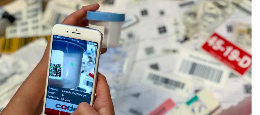Hand holding phone to scan a sample jar. Multiple barcoded labels in the background.